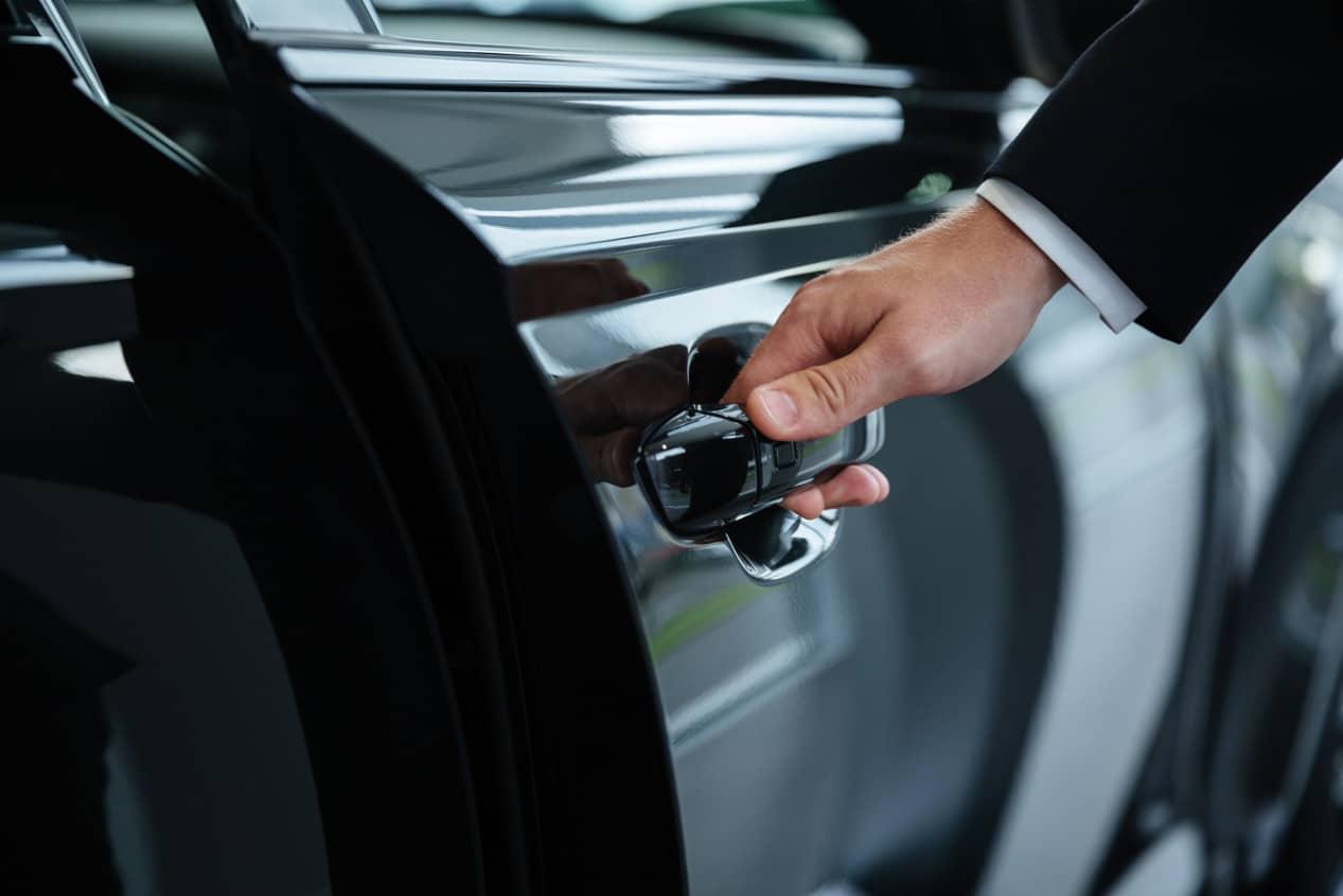 Autista apre portiera auto durante un servizio di noleggio con conducente